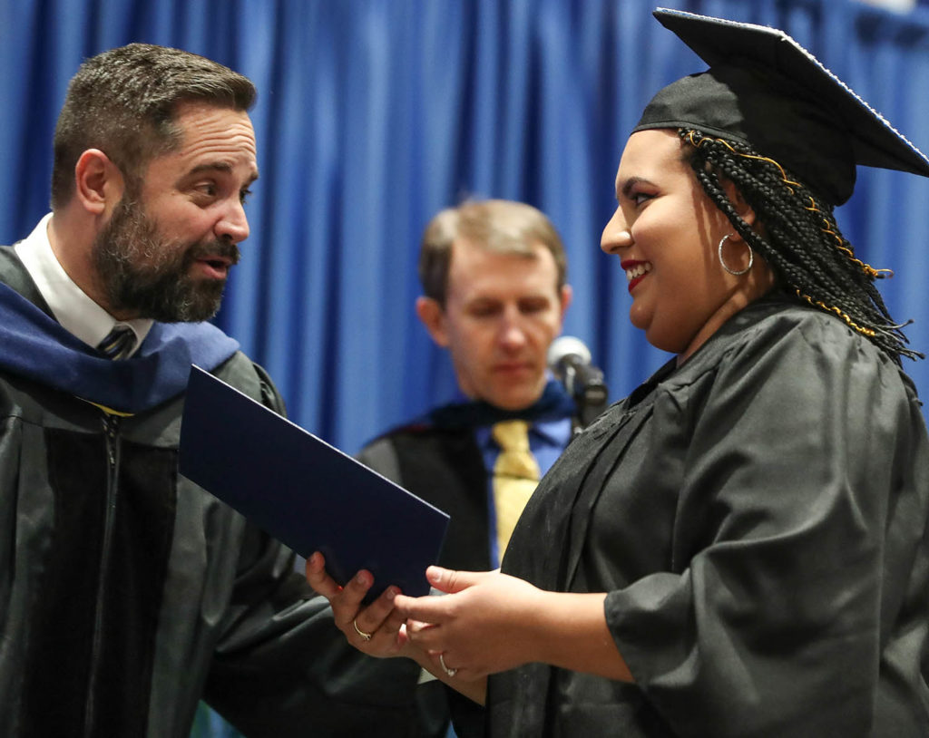 College of Arts and Sciences Dean Ryan Teten congratulates Esthefany Lopez-Cruz during Friday's winter commencement at UNK. Lopez-Cruz, a first-generation college graduate, earned a bachelor's degree in Spanish translation and interpretation. (Photos by Corbey R. Dorsey, UNK Communications)