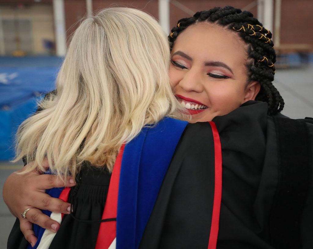 UNK associate Spanish professor Michelle Warren embraces Esthefany Lopez-Cruz prior to Friday's winter commencement.