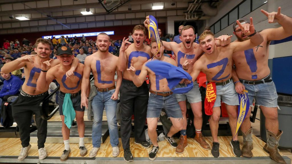 "Brockton Sterling, fourth from left, and his Colorado School of Mines football teammates cheer for his sister, Bailee, and the Loper volleyball team at Saturday's national championship. ""We don't mind being Lopers for a few hours this weekend. It's been well worth it,"" Brockton said. (Photo by Corbey R. Dorsey, UNK Communications)"