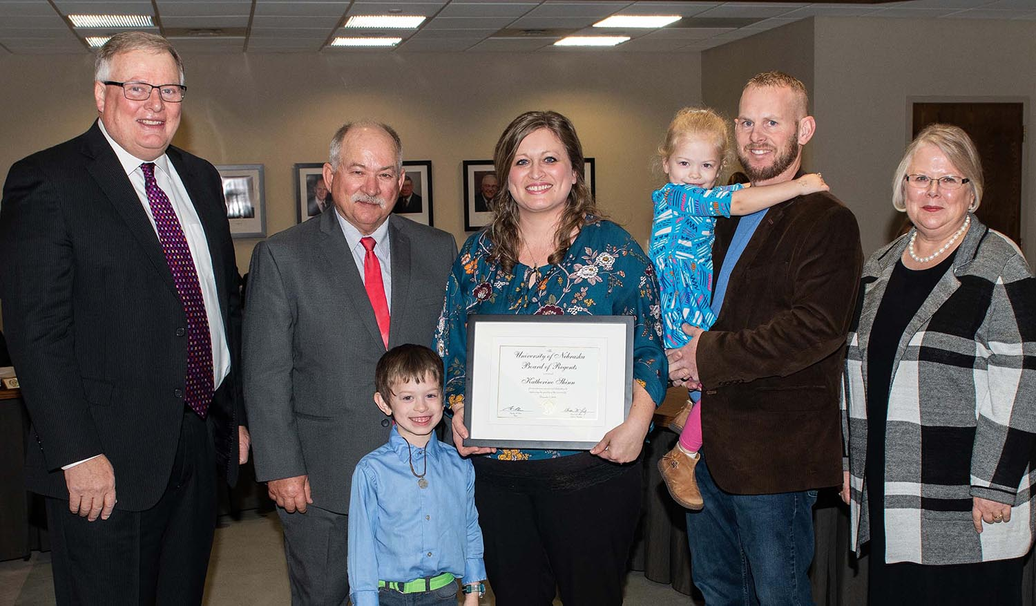 Katherine Shinn, middle, was recognized with the KUDOS award at Thursday's University of Nebraska Board of Regents meeting, which was attended by, from left, UNK Chancellor Doug Kristensen, Regent Paul Kenney, Shinn's son Landon, daughter Evelyn and husband Nolan and NU interim President Susan Fritz.