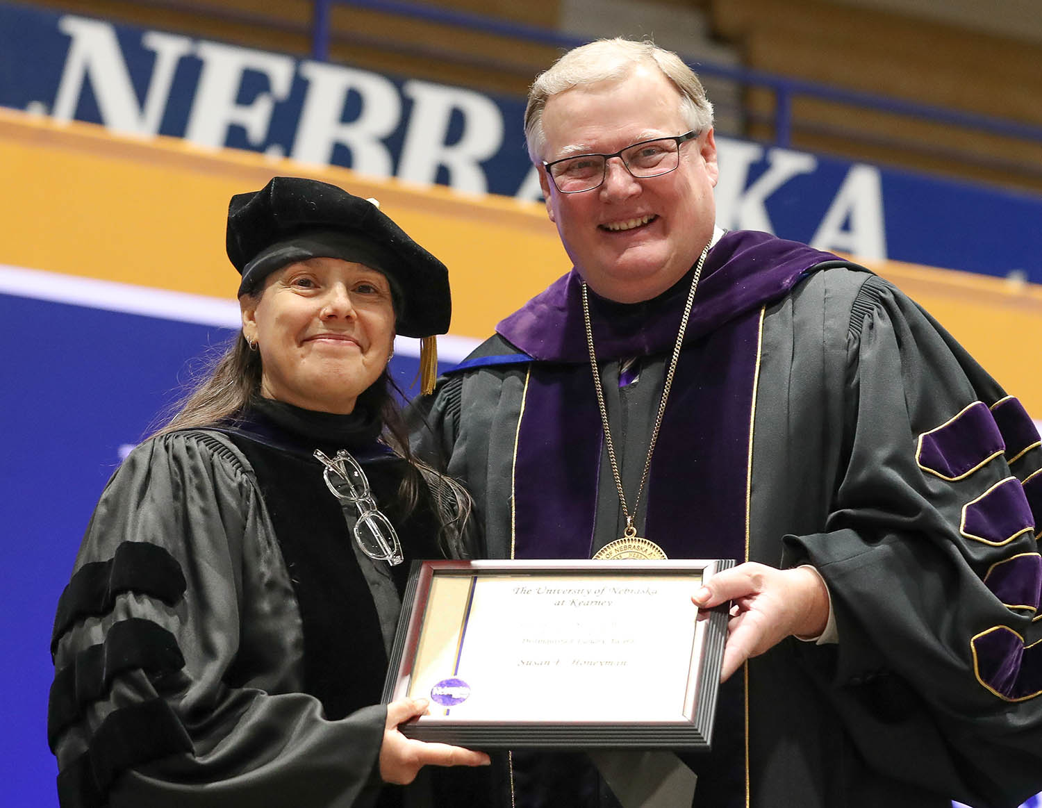 Susan Honeyman, a professor in UNK's Department of English, receives the Leland Holdt/Security Mutual Life Distinguished Faculty Award from Chancellor Doug Kristensen during Friday's winter commencement at the Health and Sports Center. (Photo by Corbey R. Dorsey, UNK Communications)