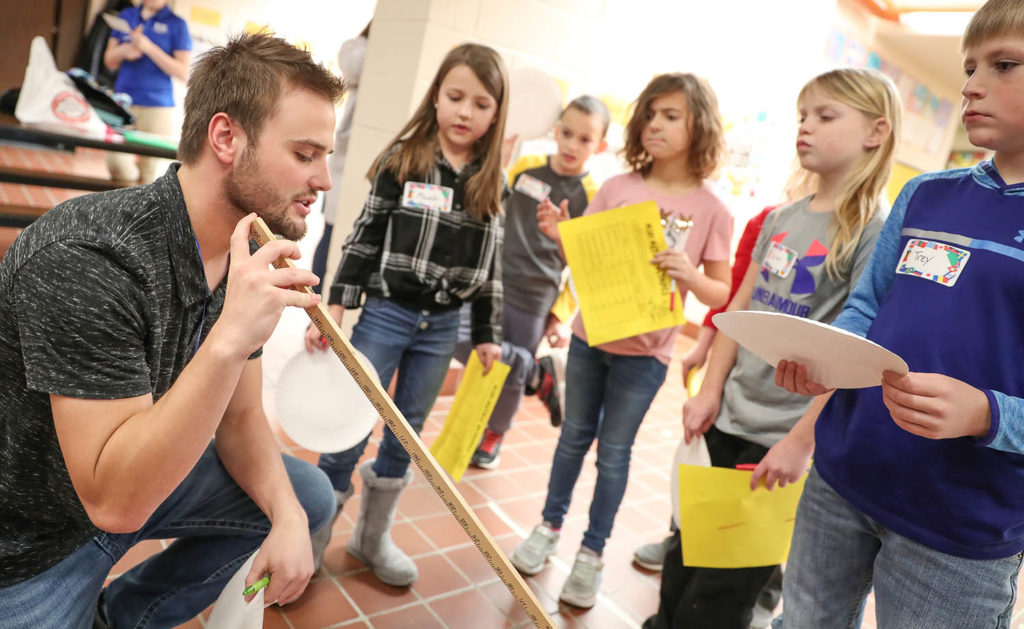 UNK senior Jesse Ritterbush, left, an elementary education major from Ord, prepares students for the paper plate discus Friday during the Measurement Olympics at Windy Hills Elementary School in Kearney. Ritterbush will student teach next semester at Meadowlark Elementary School in Kearney.