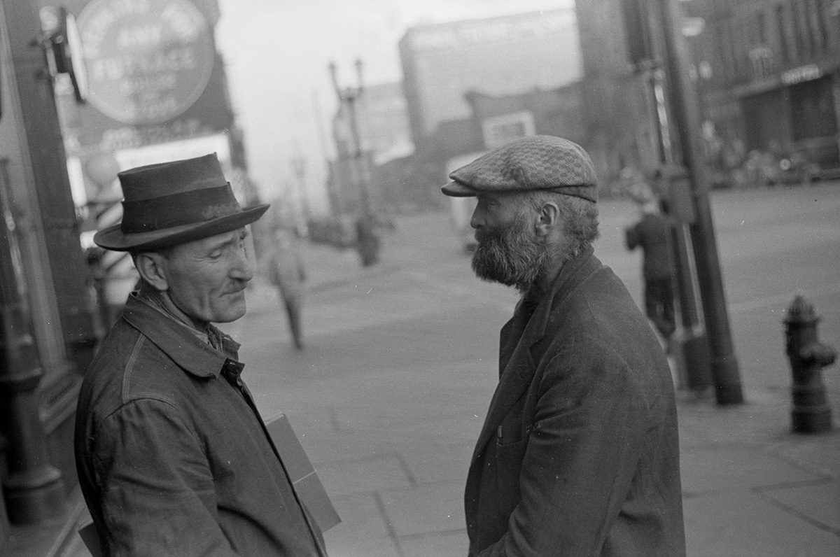 """Two hobos are pictured along lower Douglas Street in Omaha in this 1938 image captured by photographer John Vachon. The photo caption referred to Omaha as """"one of the hobo centers of the West."""" (Library of Congress)"""