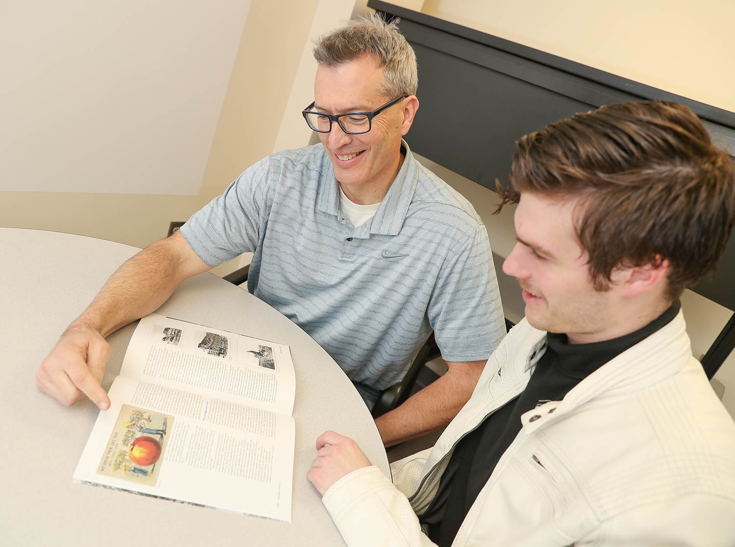 "UNK geography professor Jason Combs, left, and his son Tate, a junior at UNK, worked together on a research project studying Nebraska's ""exaggeration postcards."" Their project is featured in the Winter 2019 edition of Nebraska History Magazine. (Photo by Corbey R. Dorsey, UNK Communications)"