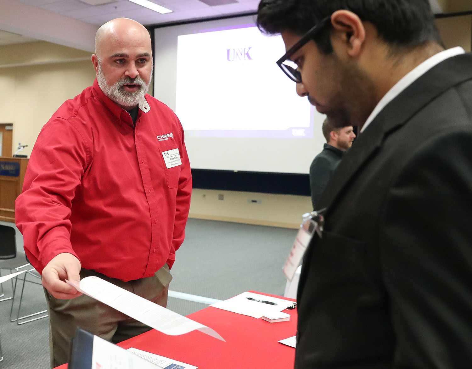 Mike Catlett, infrastructure and support manager for Grand Island-based Chief Industries, left, meets with a student Thursday during a career event hosted by UNK's Cyber Systems Department. (Photos by Corbey R. Dorsey, UNK Communications)