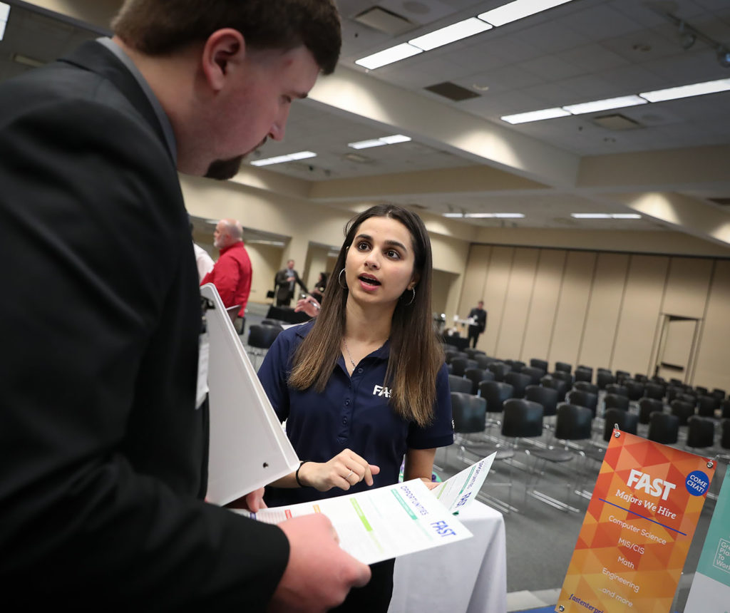 "Implementation consultant Diksha Ahuja, right, shares information about Centennial, Colorado-based Fast Enterprises with UNK senior Connor Slagle during Thursday's career event hosted by UNK's Cyber Systems Department. ""It was incredibly easy for me to find a job. I applied to several companies and received several job offers, this just happened to be the best one,"" said Ahuja, who earned a degree in computer science from the University of Nebraska-Lincoln."