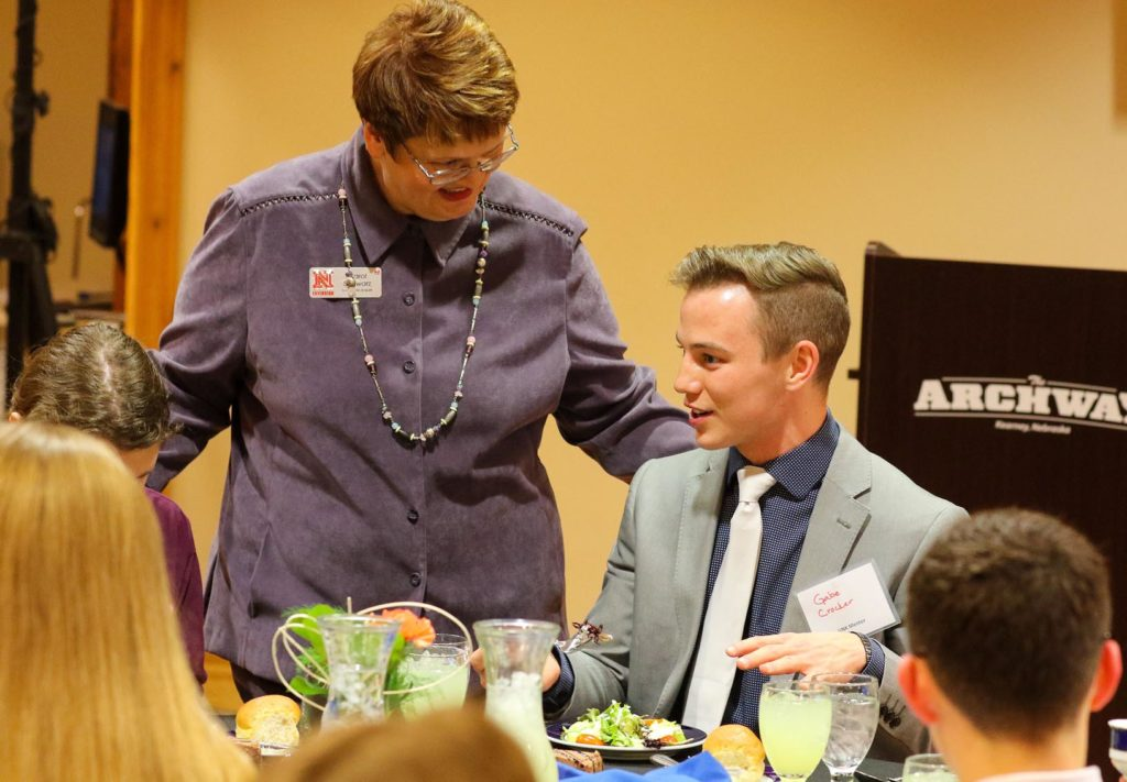 UNK senior Gabe Crocker chats with Carol Schwarz, an educator with Nebraska Extension in Buffalo County, during Friday evening's Skills for Success session on dinner etiquette at The Archway in Kearney. Students from UNK's Sigma Phi Epsilon fraternity and Alpha Phi sorority serve as volunteer mentors for the program.