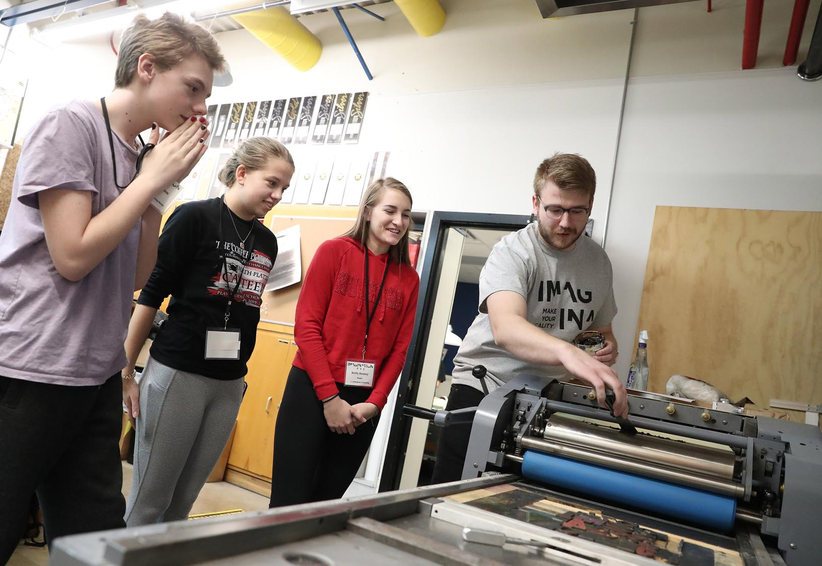 UNK junior Evan Ludwig, right, a visual communication and design major from Grand Island, leads a letterpress printing workshop during Imagination Day.