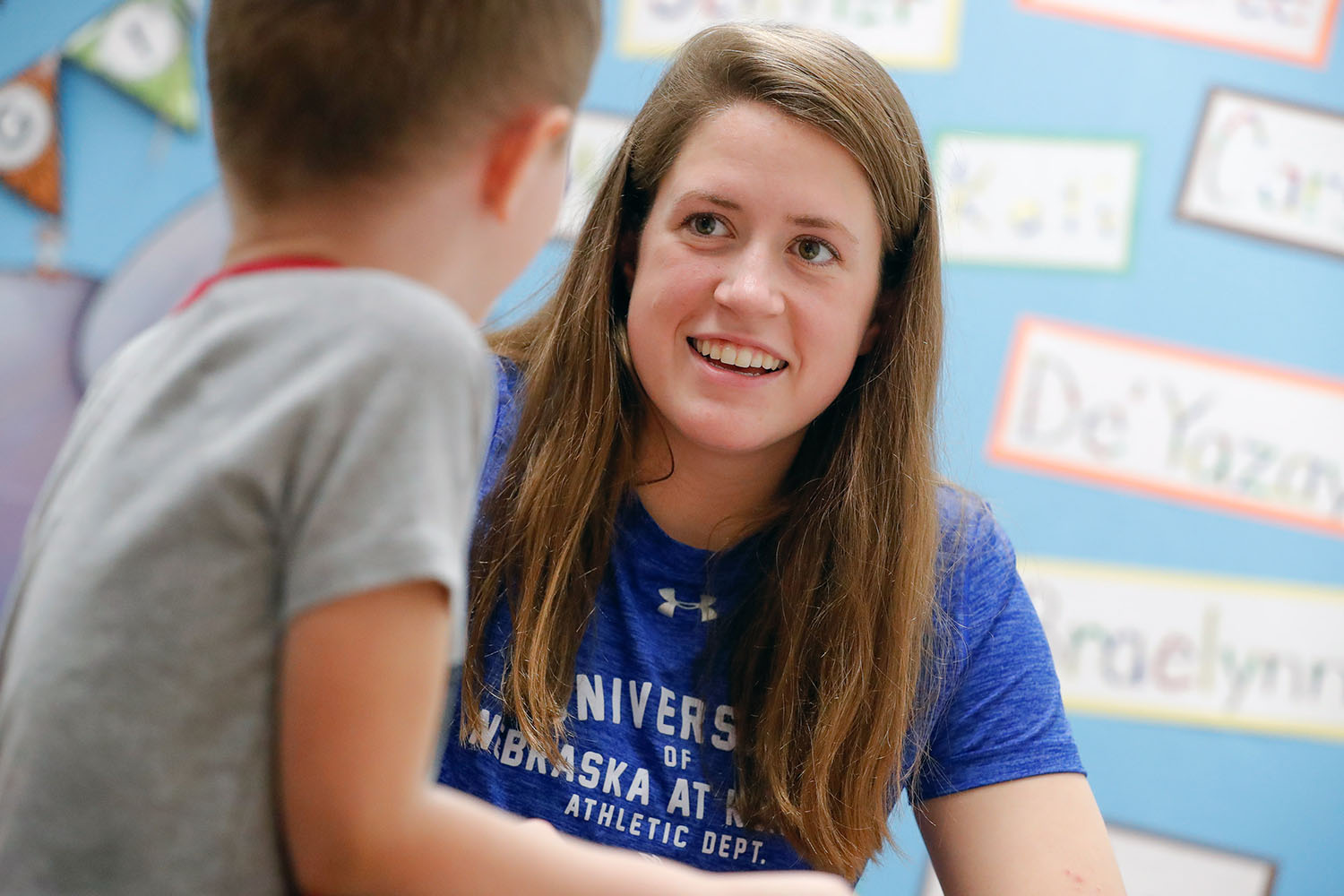 UNK swimmer Mikara Feit, a 7-12 special education major, chats with a kindergartner at Kenwood Elementary School in Kearney as part of the Loper AthLEADS program, which encourages UNK student-athletes and coaches to make a difference on campus and in the community.