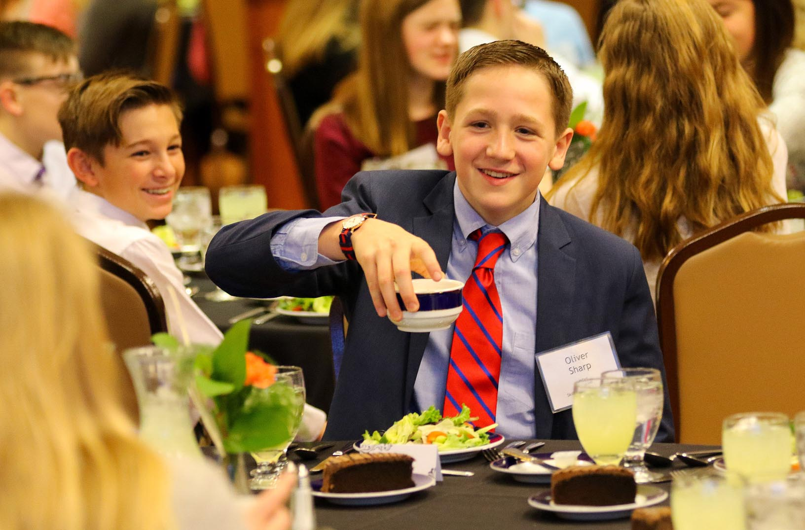 Kearney Catholic seventh grader Oliver Sharp is looking sharp in a suit and tie during Friday evening's Skills for Success session on dinner etiquette at The Archway in Kearney.
