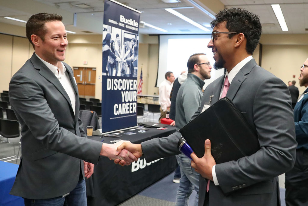 UNK senior Thomas Russell, right, introduces himself to JR Rother, director of information systems for Grand Island-based Bosselman Enterprises, during Thursday's career event hosted by UNK's Cyber Systems Department.