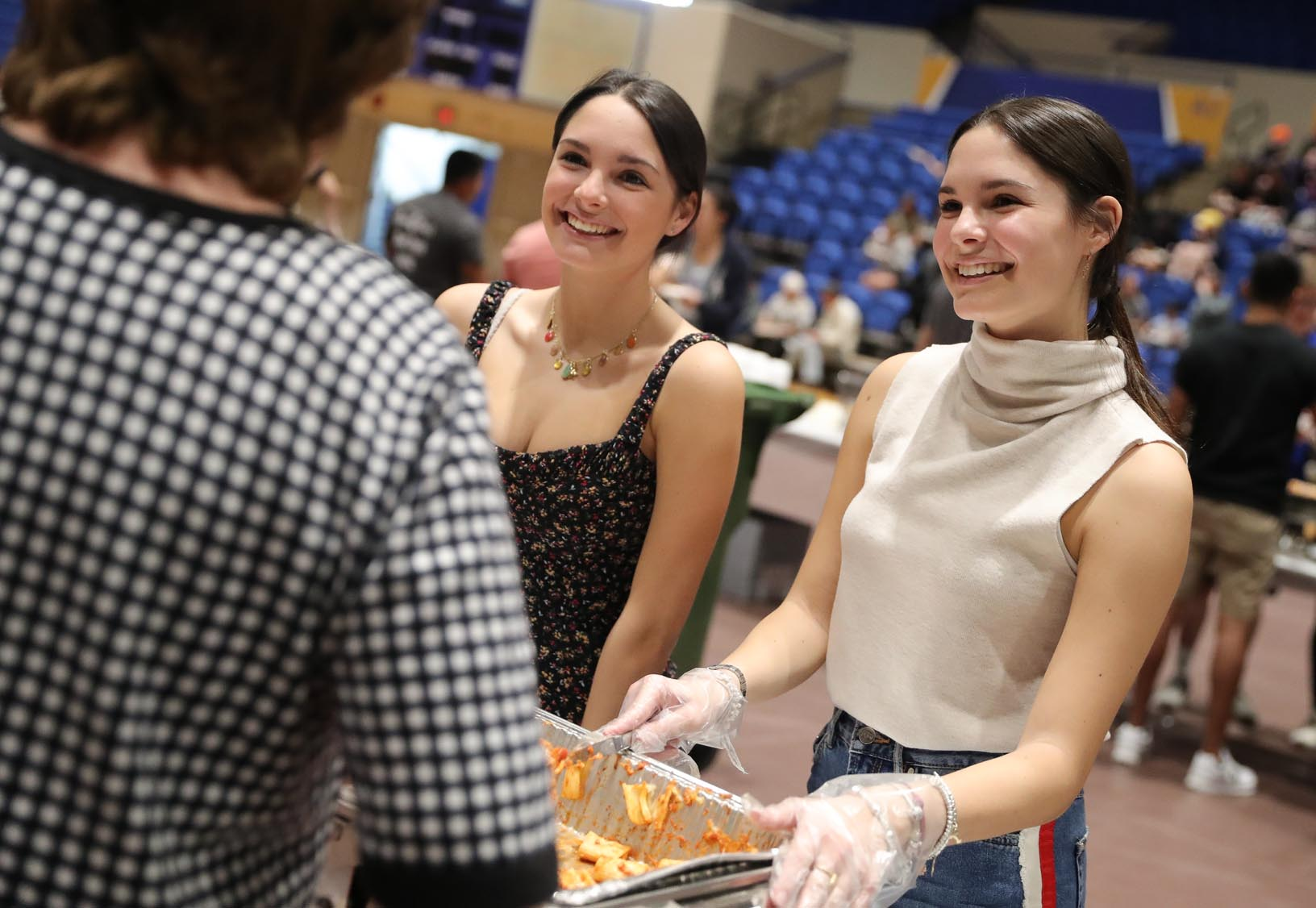 Twin sisters Sara, left, and Martina Mangiacavalli of Italy chat with guests while serving a baked pasta dish during Sunday's Scott D. Morris International Food and Cultural Festival.