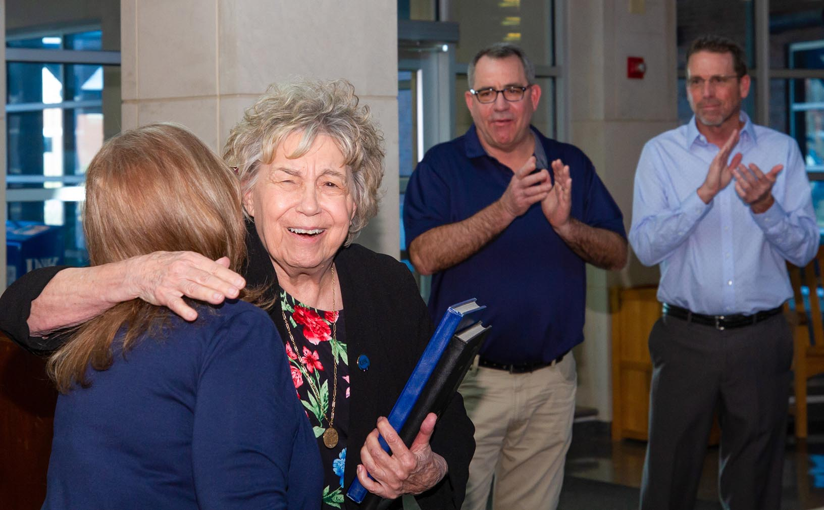 Patricia Hoehner, second from left, a professor of educational administration at UNK, hugs interim College of Education Dean Grace Mims during Friday's dedication of the Hoehner Family Conference Room. (Photos by Chase Harmon, UNK Communications)