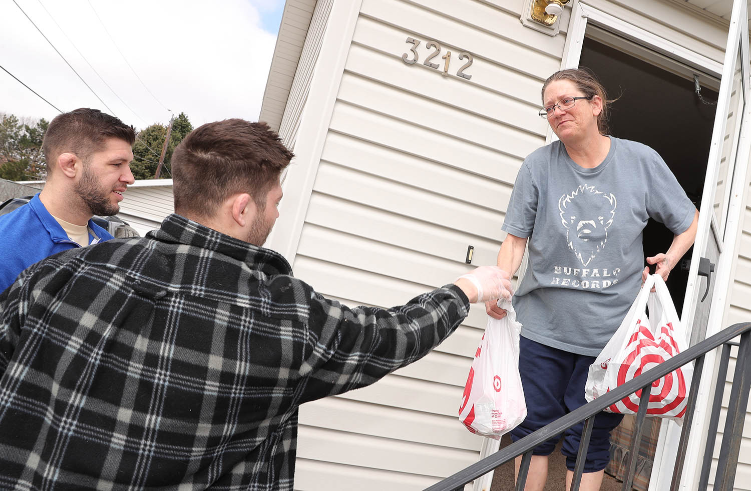 UNK wrestlers Anthony Mancini, left, and Matt Malcom deliver meals to Paula Cowen on Tuesday while volunteering for Hot Meals USA. (Photos by Corbey R. Dorsey, UNK Communications)