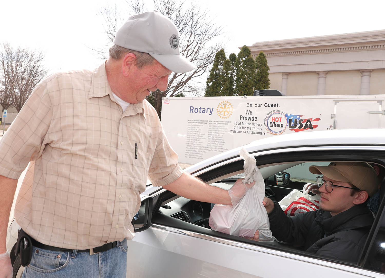 Hot Meals USA founder and director Dick Cochran, left, hands a meal delivery to UNK wrestler Walker Johnson on Tuesday. UNK wrestlers and coaches are volunteering with the local nonprofit, which is providing free meals to people impacted by the ongoing coronavirus (COVID-19) pandemic.