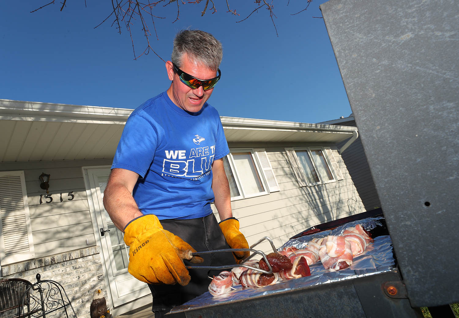 """UNK exercise science professor Greg Brown grills bacon-wrapped venison steaks in his front yard Tuesday evening during the first """"front porch celebration"""" in Kearney. Brown started the event so neighbors can remain connected during the coronavirus outbreak while following social distancing guidelines. (Photos by Corbey R. Dorsey, UNK Communications)"""