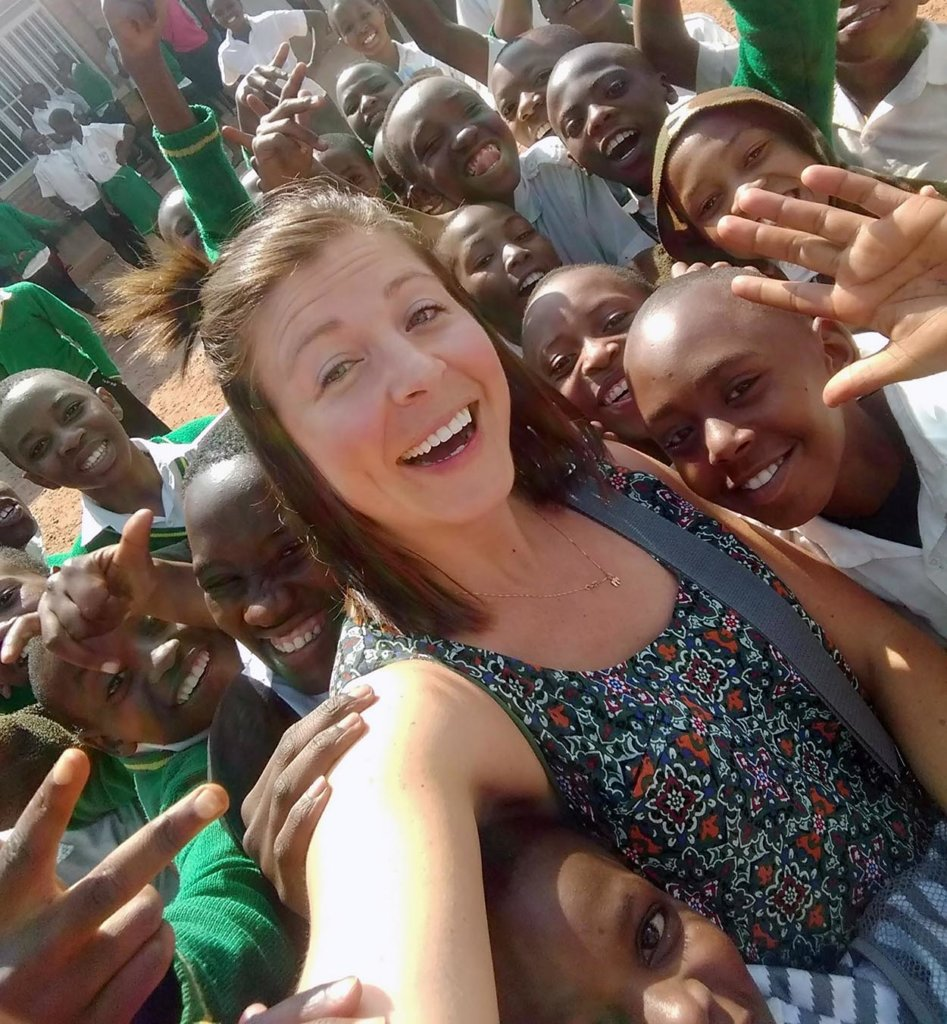 Megan Helberg takes a selfie with a group of local children during a July 2018 trip to Rwanda.