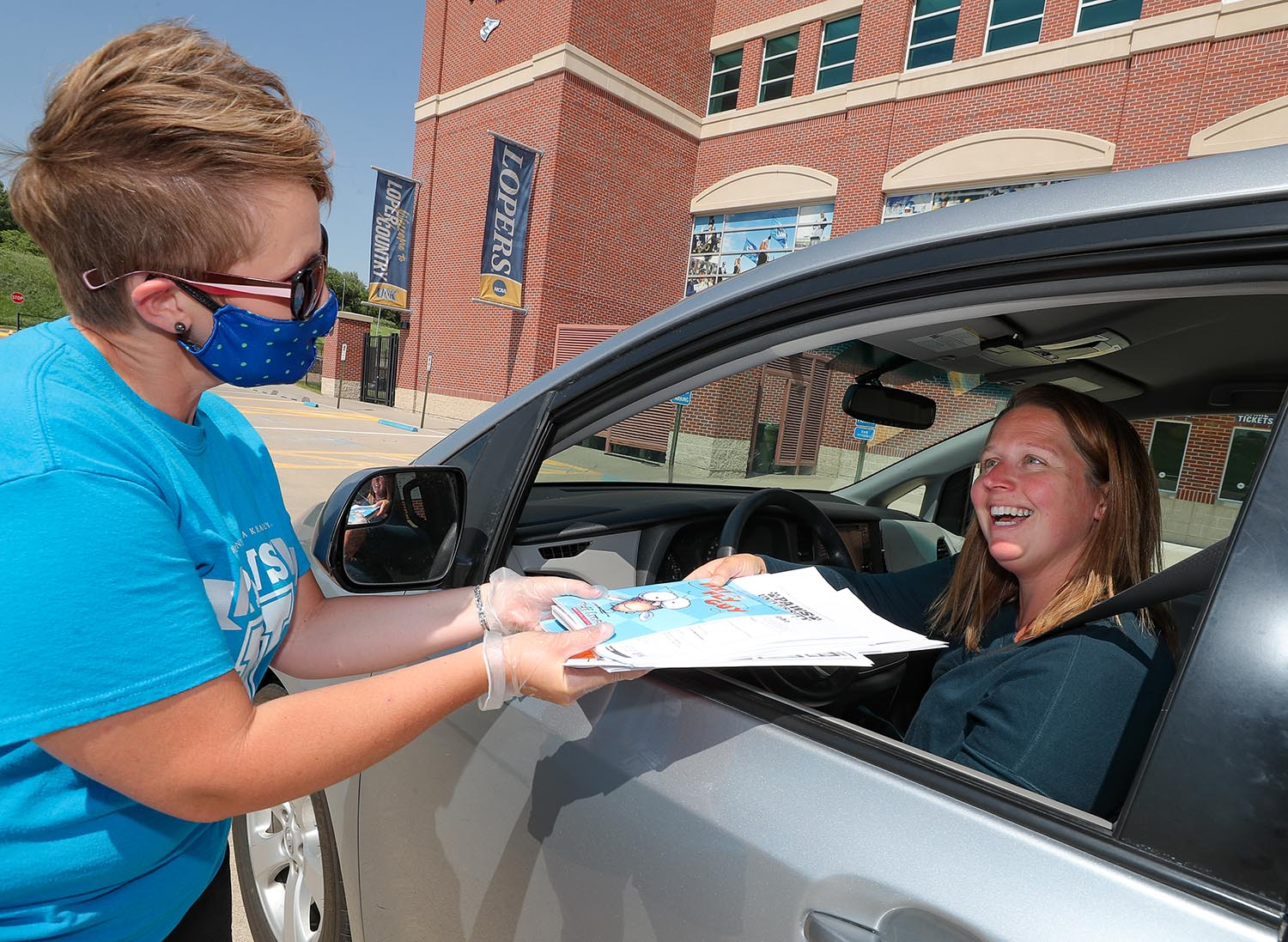 PAWS University director Amy Nebesniak, left, hands educational materials to Kearney resident Brooke Ward on Monday afternoon at UNK's Cope Stadium. PAWS University: Home Edition, a UNK summer program, allows area families to access a variety of curriculum-based activities for elementary students through take-home kits distributed each week. (Photos by Corbey R. Dorsey, UNK Communications)