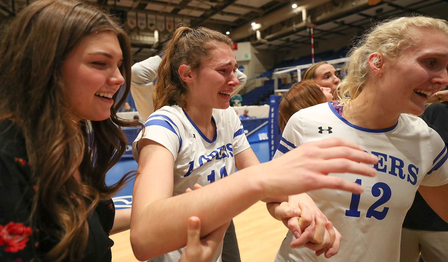 UNK graduate assistant athletic trainer Hailey McNee, left, celebrates with the Loper volleyball team last December after a five-set victory over Concordia-St. Paul to win the Central Regional. McNee begins her new job this week as a full-time athletic trainer at the University of Wyoming. (Photo by Corbey R. Dorsey, UNK Communications)