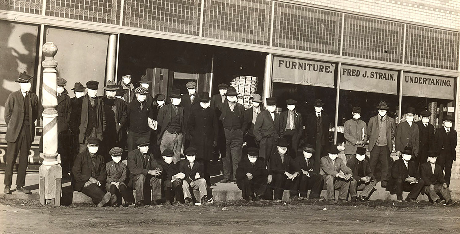 A group of men wearing protective face coverings are pictured in front of a Shelby business during the Spanish flu outbreak in December 1918. (Nebraska State Historical Society)