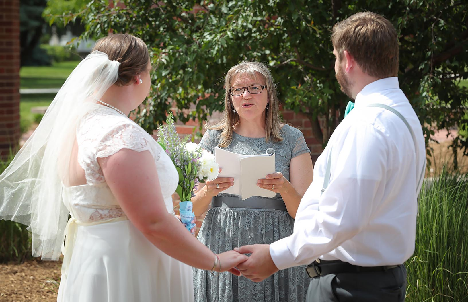 UNK biology professor Kim Carlson, center, officiates Saturday as Alexis Page and Nick Hobbs are married on the UNK campus.