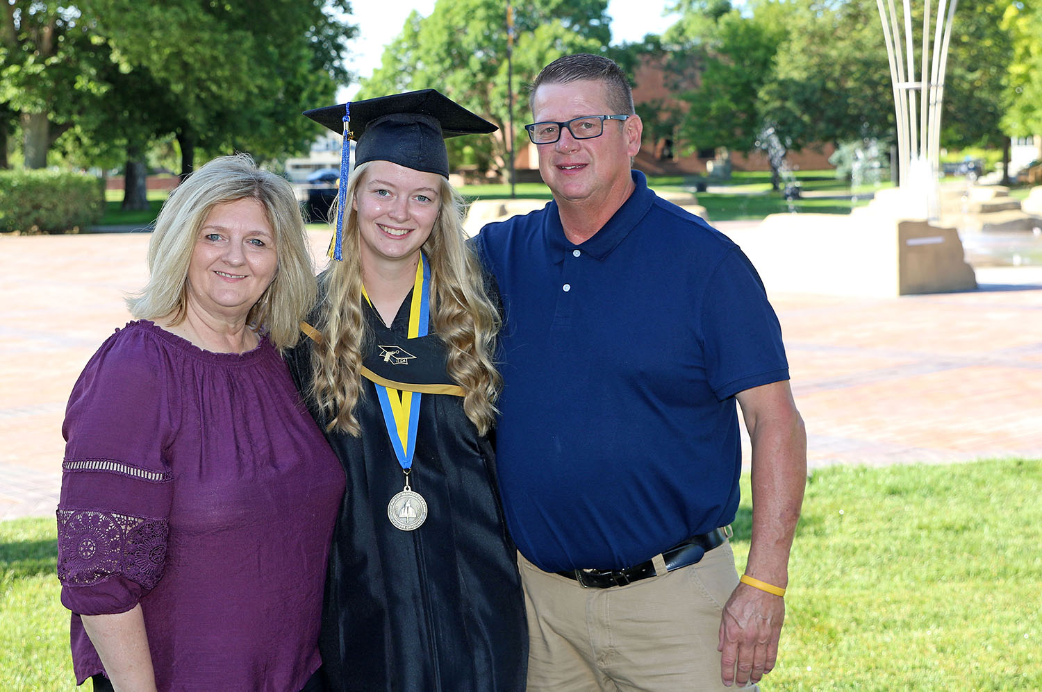 UNK graduate Madison Clausen of Norfolk poses for a photo with her parents Penny and Mark before Friday's commencement ceremony. Clausen earned a bachelor's degree in communication disorders and she'll pursue a master's in speech-language pathology at UNK this fall.