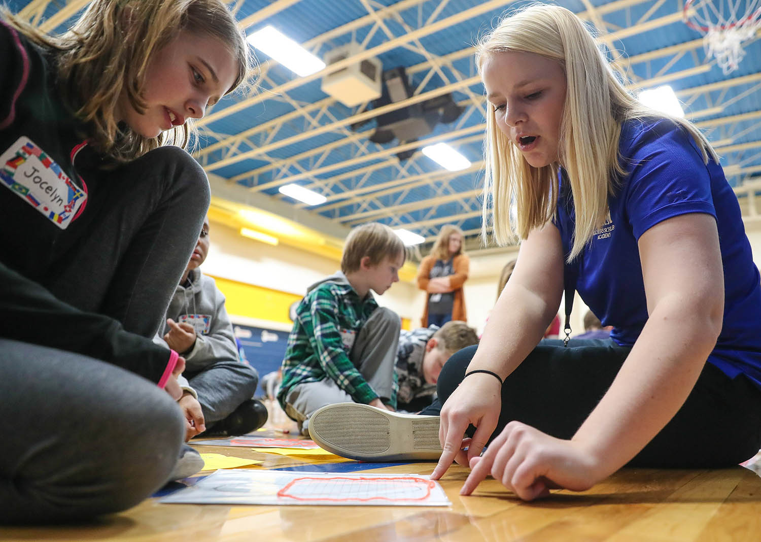 Shelby Pocock of Kearney, right, a member of UNK's Teachers Scholars Academy, works with students at Windy Hills Elementary School during a Measurement Olympics event last December. (Photo by Corbey R. Dorsey, UNK Communications)