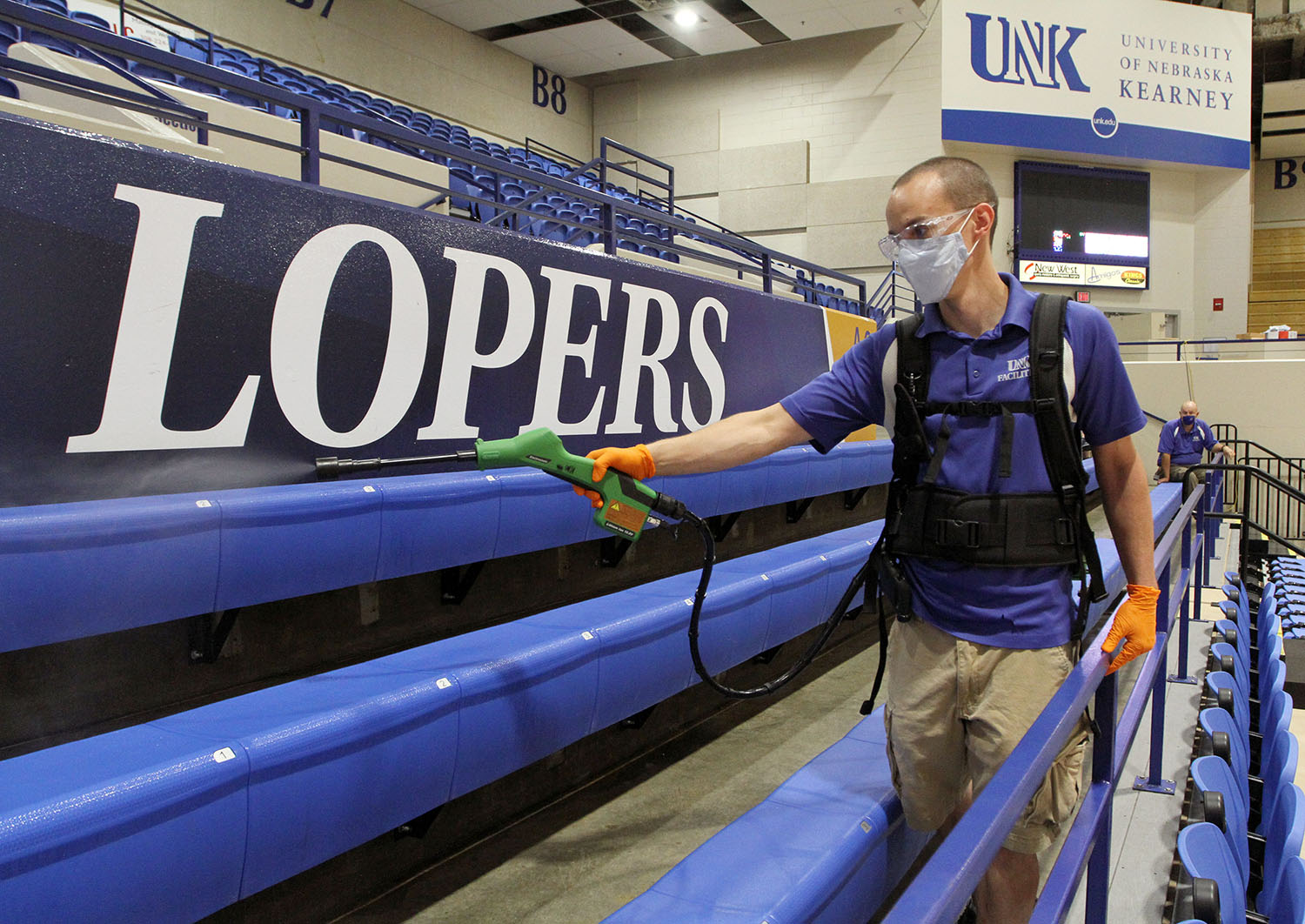 Chris Blocher, lead custodian for UNK's athletic facilities, uses an electrostatic sprayer to disinfect surfaces inside the Health and Sports Center. Electrostatic sprayers apply a positive charge to liquid disinfectants as they pass through the nozzle. The positively charged disinfectant is attracted to negatively charged surfaces, allowing the disinfectant to efficiently coat hard, nonporous surfaces.