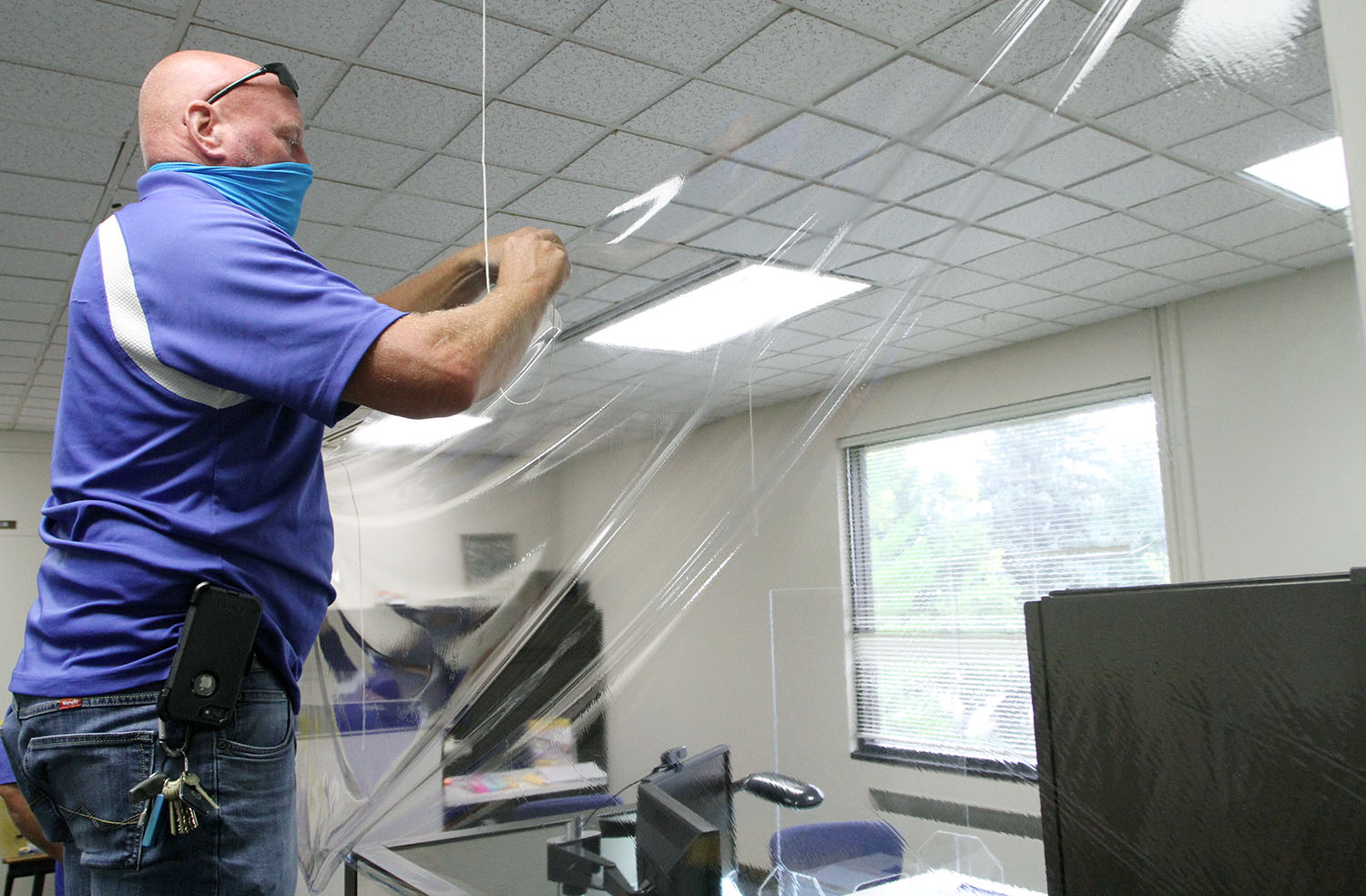 Dan Hill, building services supervisor with UNK Facilities Management and Planning, hangs a plastic barrier around a work station inside Warner Hall. Facilities Management is installing clear, plastic barriers in high-traffic areas and spaces where there's regular interaction between people.