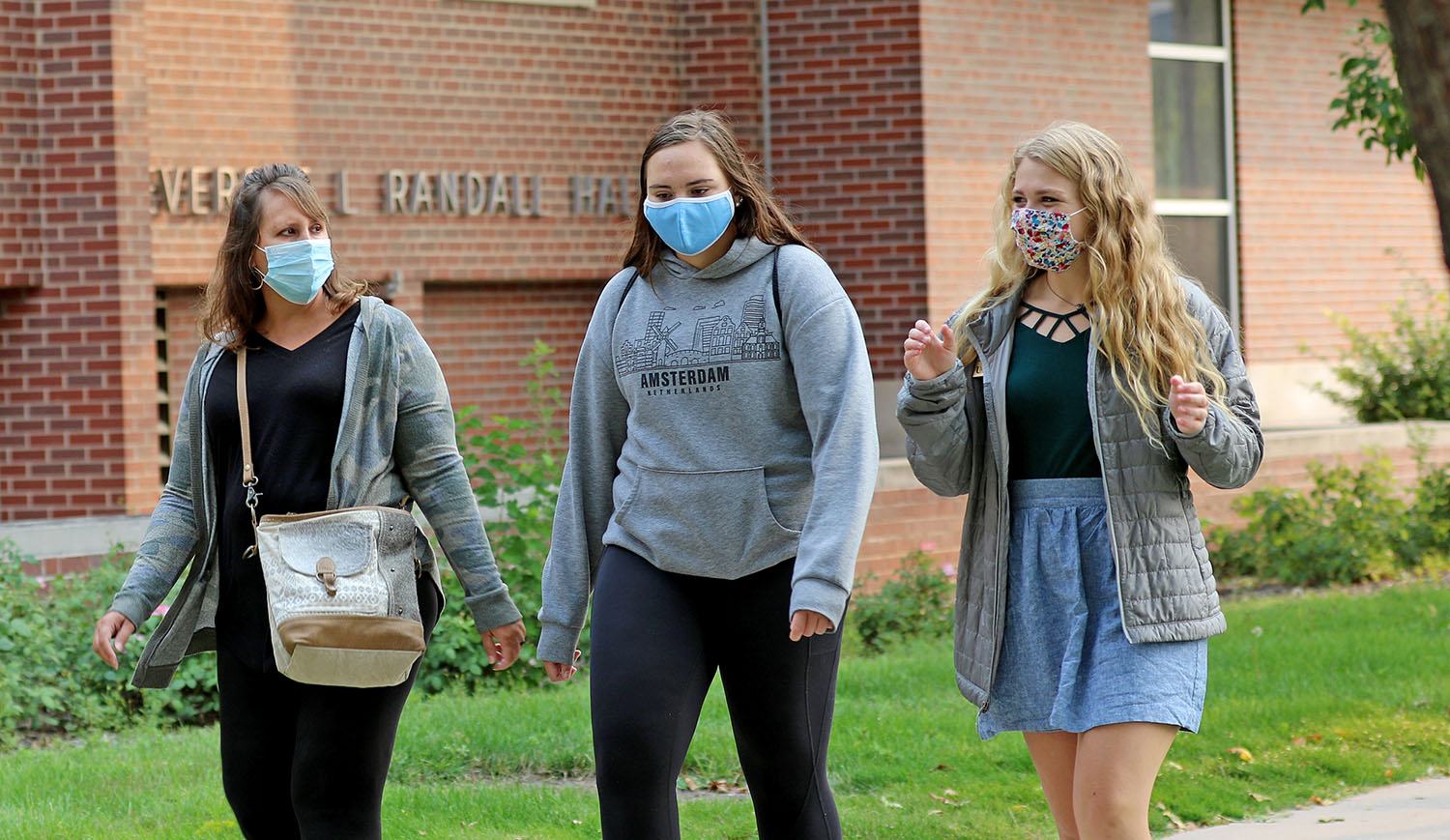 UNK campus visit assistant Holly Rockenbach, right, leads a tour for prospective student Morgan Allen of Blue Hill, center, and her mother Tricia on Thursday morning. UNK resumed in-person visits this week.