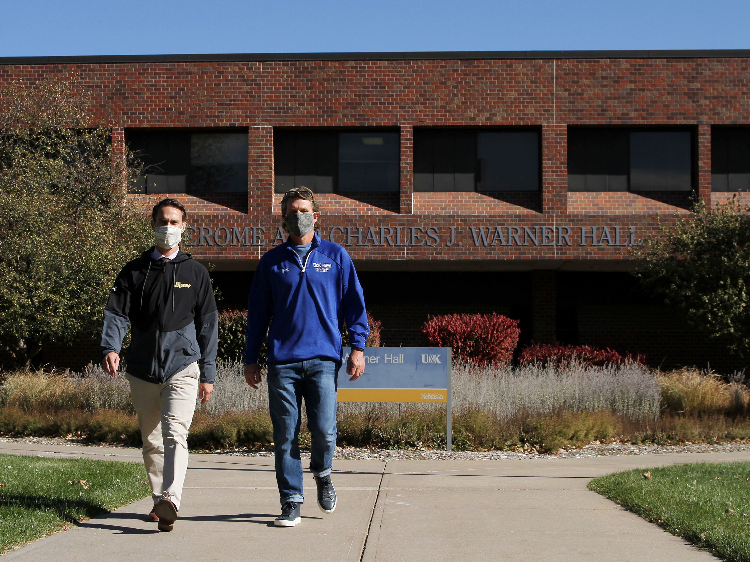 """Matt Bice, left, associate dean of graduate studies and director of undergraduate research and creative activity, and Mark Ellis, dean of graduate studies, regularly organize """"walk-and-talk"""" meetings on the UNK campus. They average more than 10,000 steps per day."""