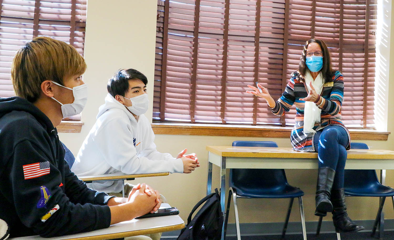 Kyohei Nakamura, left, and Kazuki Ishikawa, center, listen to instructor Lisa Terry as she leads an English Language Institute course. Nakamura and Ishikawa, both from Japan, plan to study aviation at UNK.