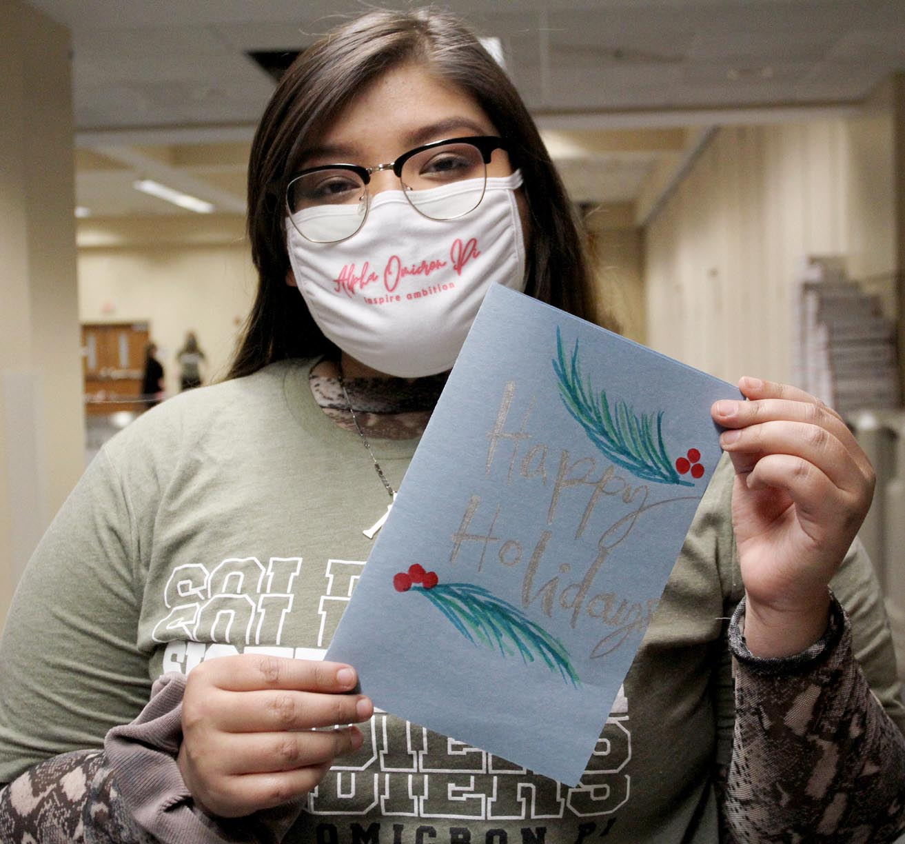 Alpha Omicron Pi member Emelin Ortega of Lexington is pictured with a holiday card she created for a U.S. military member.