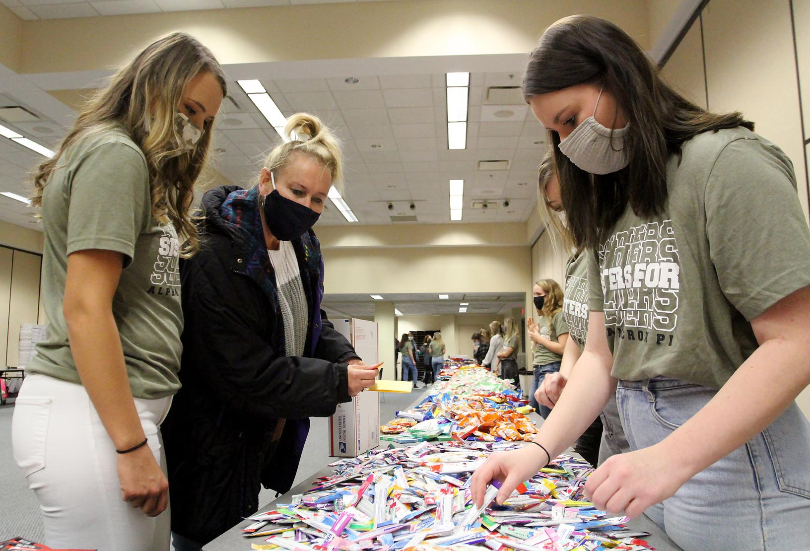 Alpha Omicron Pi members Jessie Daake of Kearney, left, and Ashley Sweet of North Platte, right, help Daake's mother Lynda create a care package for a U.S. military member during Tuesday evening's Sisters for Soldiers event.