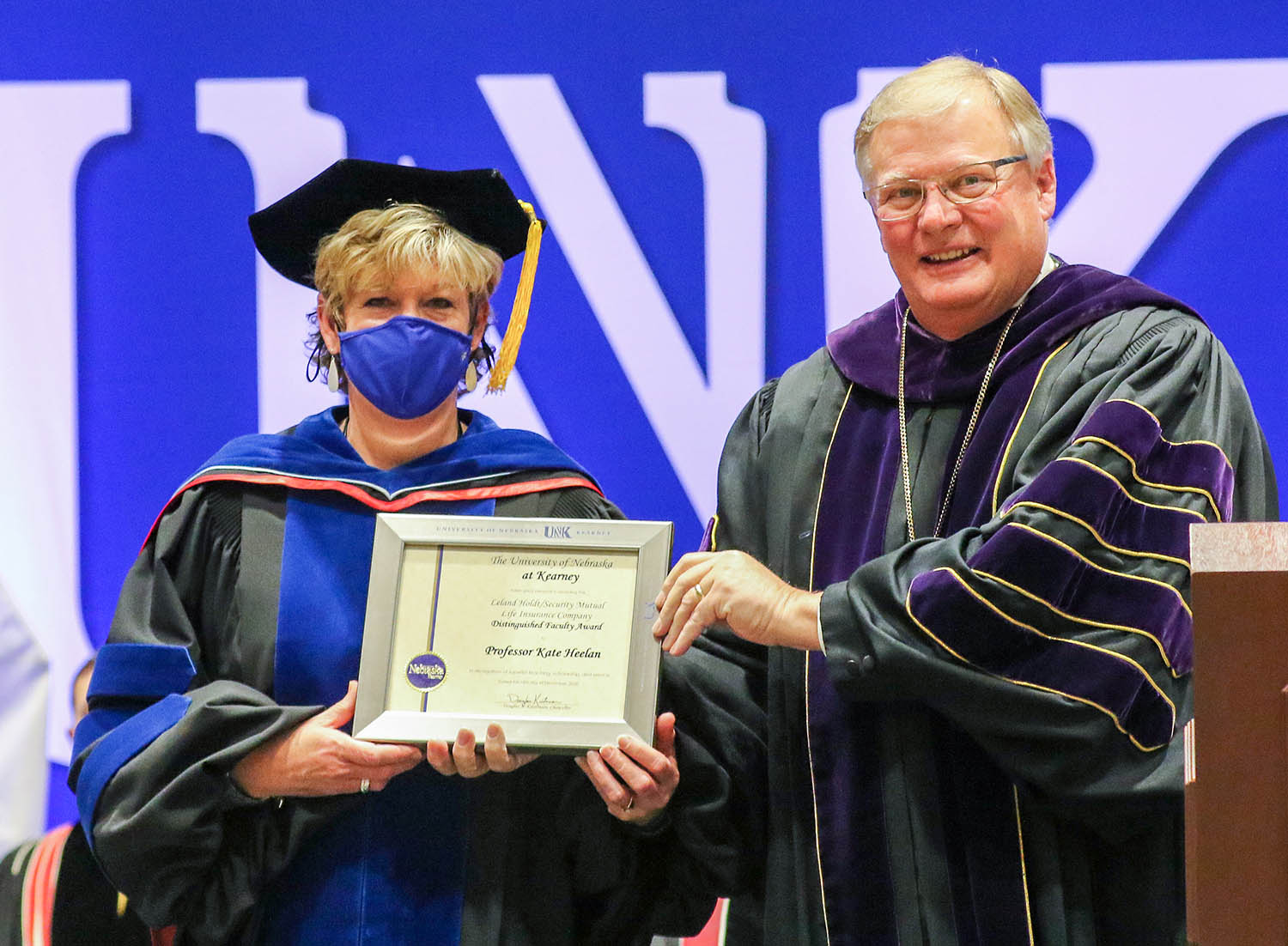 UNK Chancellor Doug Kristensen presents the Leland Holdt/Security Mutual Life Distinguished Faculty Award to exercise science professor Kate Heelan during Friday's winter commencement ceremony at the Health and Sports Center.