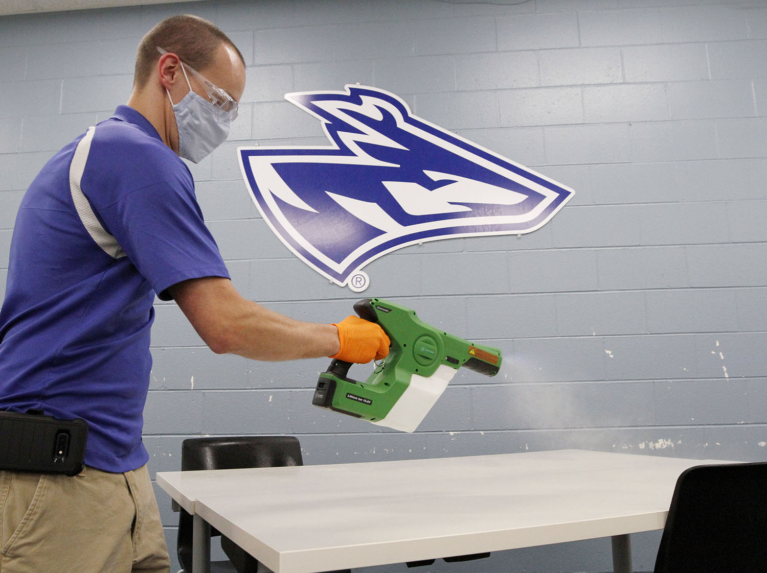 Chris Blocher, lead custodian for UNK's athletic facilities, uses an electrostatic sprayer to disinfect a table. UNK's COVID-19 response plan included enhanced cleaning protocol, as well as several other measures designed to keep the campus community safe.