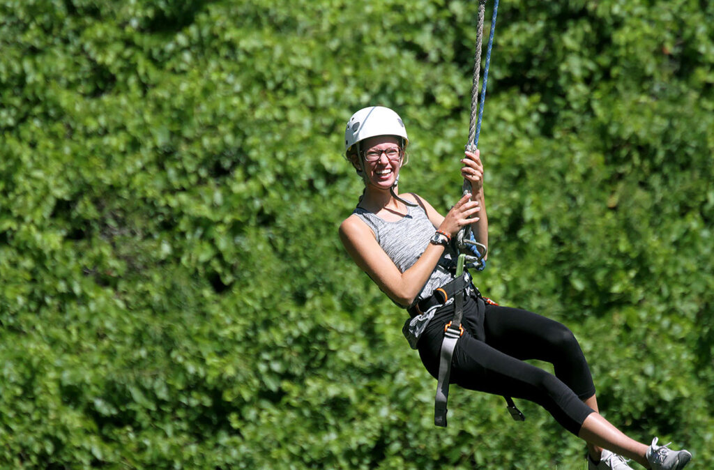 Macy Brown of Aurora soars through the Nebraska National Forest near Halsey on a zip line during UNK's First Adventure summer camp in 2019.