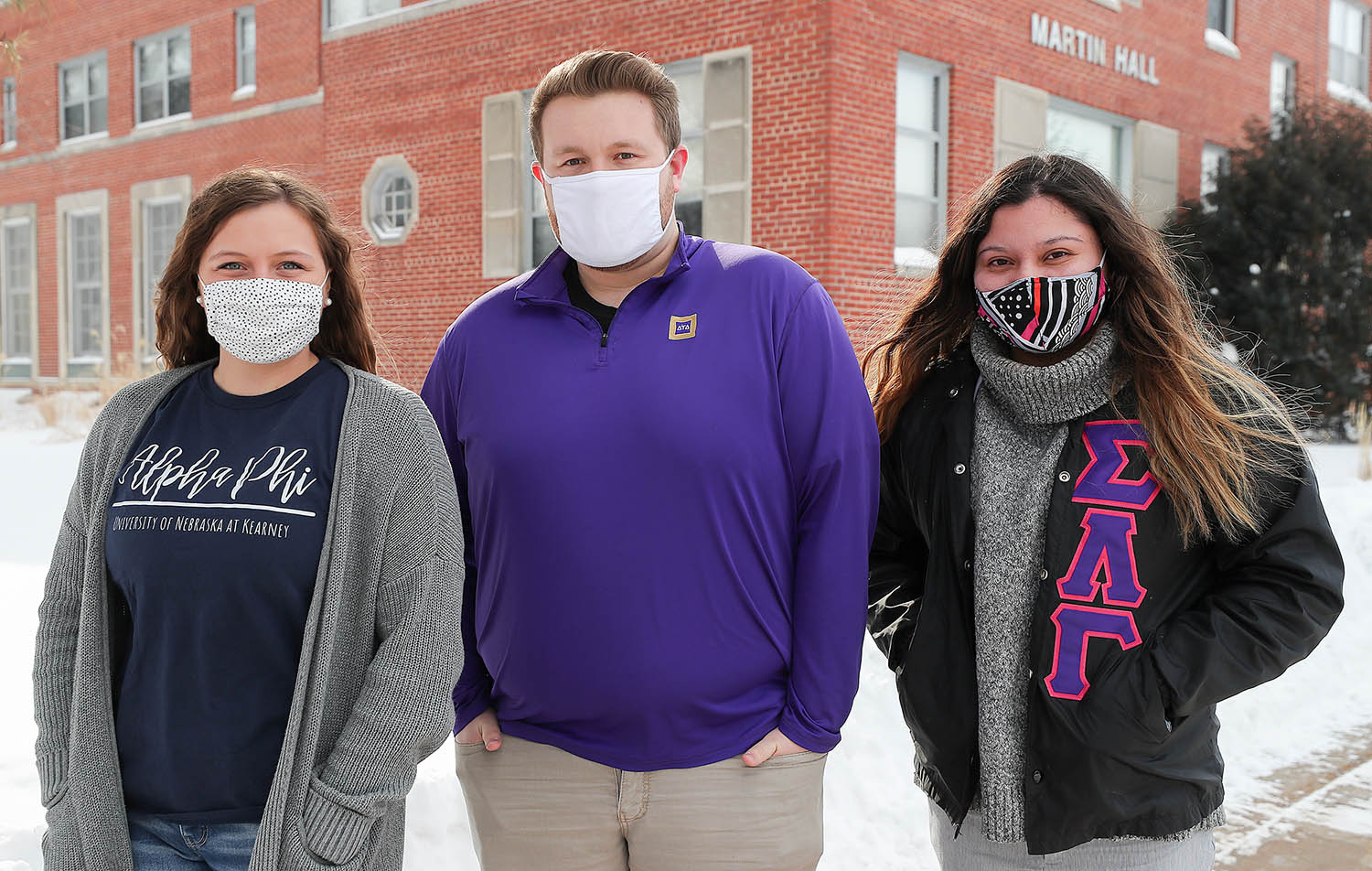 UNK Fraternity and Sorority Life members, from left, Justine Johnson of Holdrege, Brady Deprez of Omaha and Gracie Lopez of Hastings pose for a photo outside Martin Hall. A project approved Friday will replace the current fraternity and sorority housing on campus through a renovation of Martin Hall and construction of a new residence hall just north of that building. (Photo by Erika Pritchard, UNK Communications)