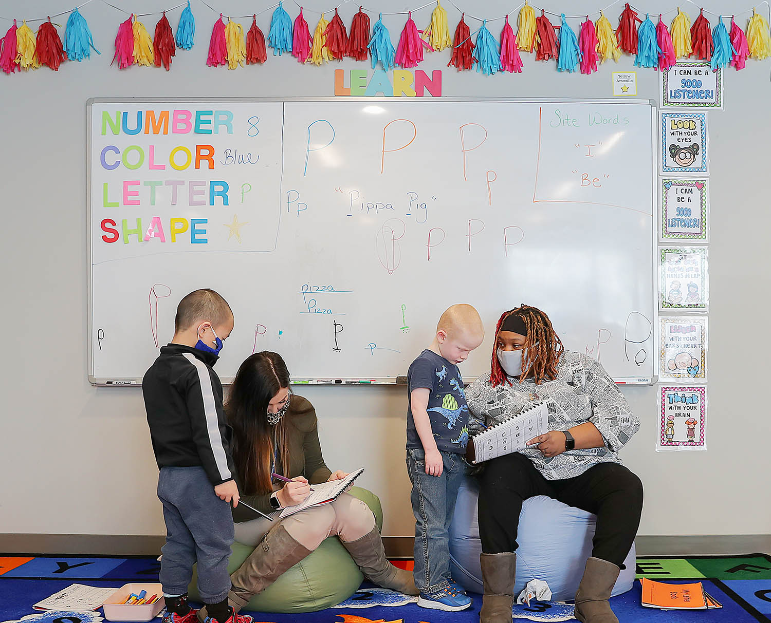 """Lead teacher Cassie Morten, second from left, and teacher assistant Phadiziana Smith-Whiteside, right, help prekindergarten students learn the letter """"P"""" during a lesson at UNK's LaVonne Kopecky Plambeck Early Childhood Education Center. Morten says Smith-Whiteside, a UNK sophomore, brings brightness and joy to the classroom."""