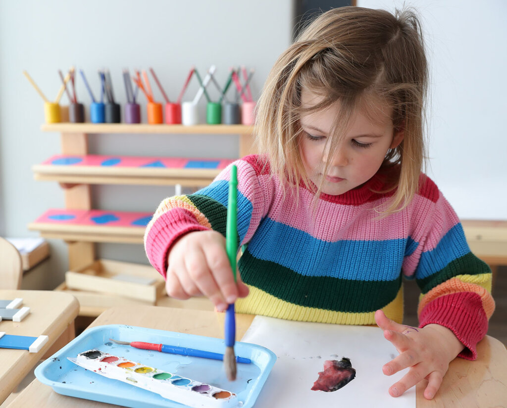 Montessori preschool student Evelynn Wetton, 3, creates a watercolor painting at UNK's LaVonne Kopecky Plambeck Early Childhood Education Center.