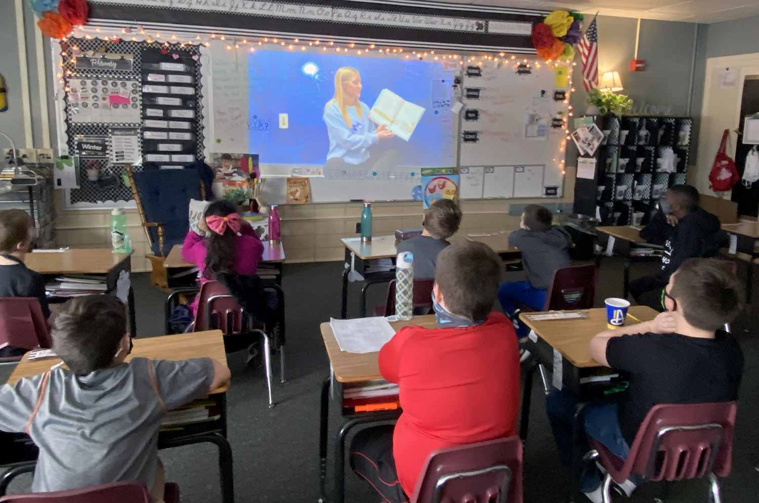 """Students in Taylor Peters' third grade class at Emerson Elementary School in Kearney watch a video of UNK cheerleader Allie Daro reading """"Cheerful Chick."""" Members of UNK's Student-Athlete Advisory Committee recorded videos of themselves reading children's books and uploaded them to the UNK Athletics YouTube channel, where they're available for any teacher or parent to use."""
