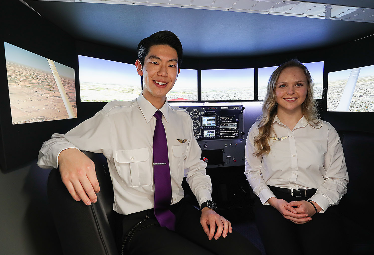 "UNK aviation students Hideharu Hayashi of Fukuoka, Japan, and Emily Farley of Waco are pictured inside the Redbird flight simulator on campus. Both students were recognized during Friday's ""Solo Wings Ceremony."" (Photo by Erika Pritchard, UNK Communications)"