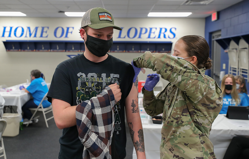 Nebraska Army National Guard member Jami Kirchner, right, gives UNK senior Jaden Powers his first dose of the COVID-19 vaccine Tuesday morning at UNK's Cope Stadium. (Photos by Erika Pritchard, UNK Communications)