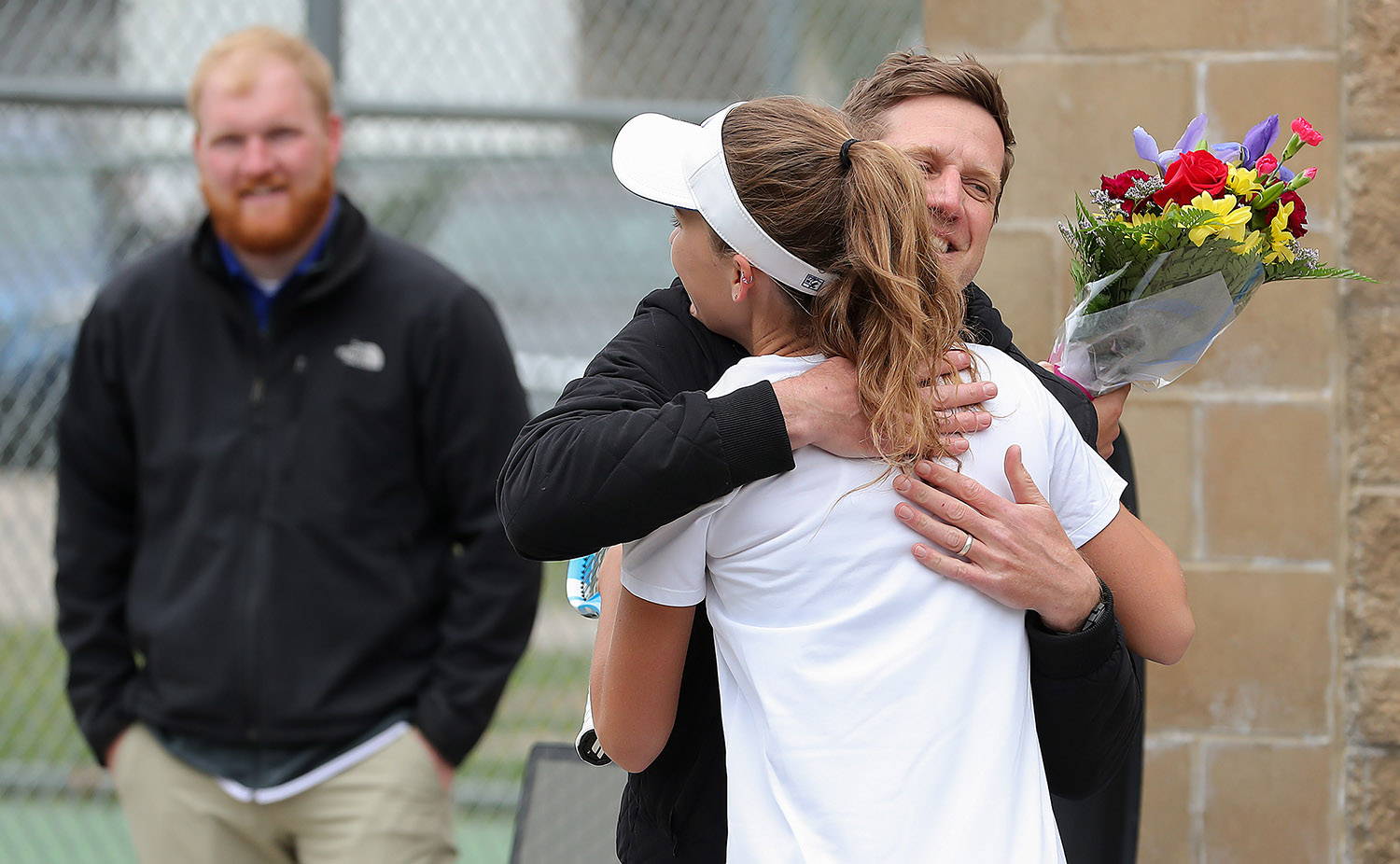 Claire Neil receives a hug from UNK head women's tennis coach Scott Shafer during an April 14 home match against Northwest Missouri State. Neil, the team's lone senior, was recognized that day.