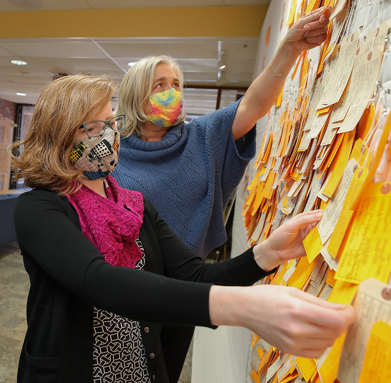 """Laurinda Weisse, front, and Michelle Warren worked together to bring the """"Hostile Terrain 94"""" exhibit to UNK's Calvin T. Ryan Library."""