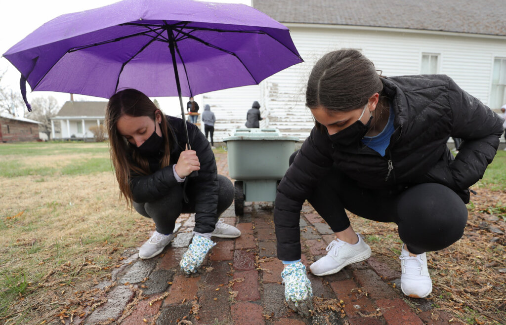 UNK students Sarah Collins, left, and Kate Kalamaja, both members of the Alpha Omicron Pi sorority, help spruce up the Buffalo County Historical Society Trails and Rails Museum during The Big Event.