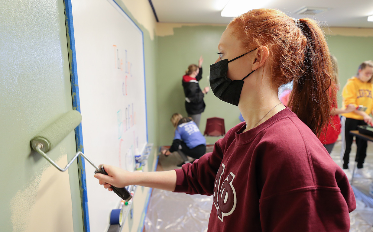 Alysa Biggs and other members of the Alpha Phi sorority paint a room for The Arc of Buffalo County on Saturday.