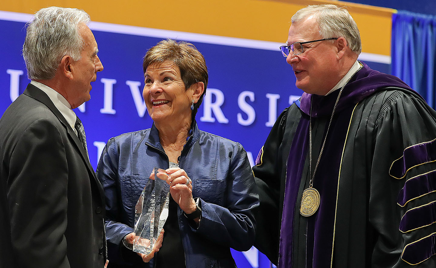 UNK Chancellor Doug Kristensen, right, presents the Ron and Carol Cope Cornerstone of Excellence Award to Pete and Jane Kotsiopulos during Friday's spring commencement ceremony at the Health and Sports Center. (Photos by Erika Pritchard, UNK Communications)