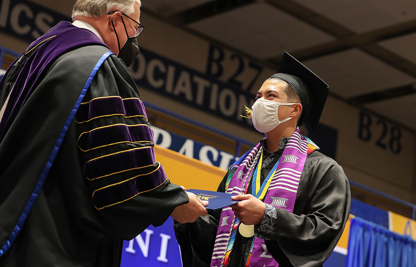 Mark Barrientos of Lexington, right, receives his degree from UNK Chancellor Doug Kristensen during Friday's commencement ceremony at the Health and Sports Center. (Photos by Erika Pritchard, UNK Communications)