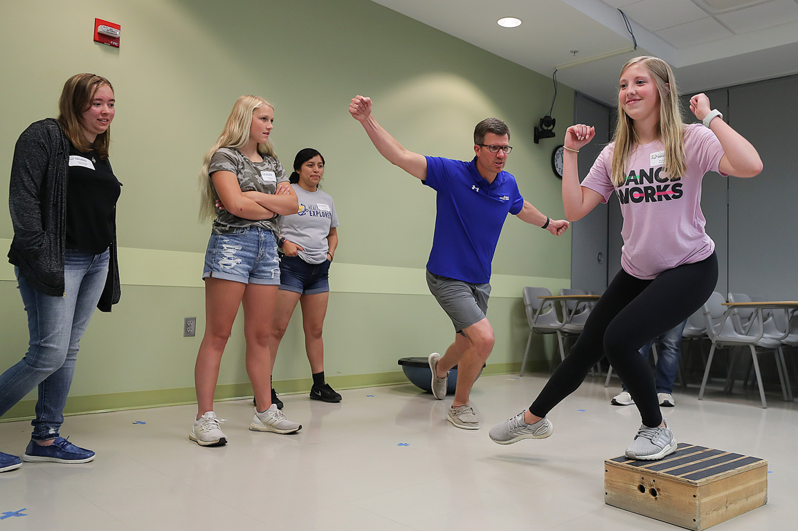 Kearney Catholic junior Erin Huddleston, right, practices a physical therapy exercise Friday during the Health Science Explorers summer camp. (Photos by Erika Pritchard, UNK Communications)